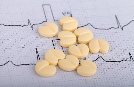 fibrillation: Heart form pills over an electrocardiogram graph