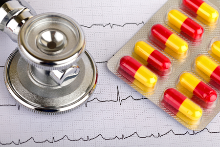 fibrillation: Electrocardiogram graph report with stethoscope and pills on it