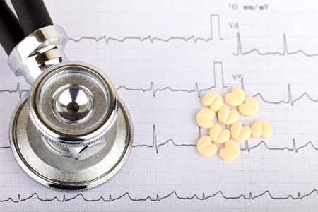 hypertension: Electrocardiogram graph report with  heart shape pills on it