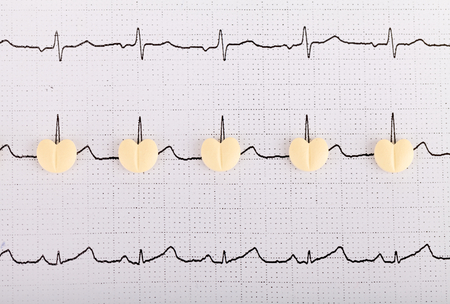 fibrillation: Electrocardiogram graph report with  heart shape pills on it