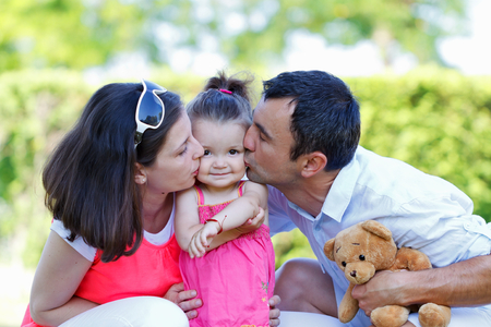 cute little girl smiling: Beautiful young couple playing with their daughter Stock Photo