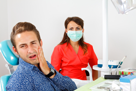 halitosis: Patient with toothache sitting in a dental cabinet Stock Photo
