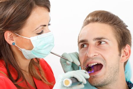 halitosis: The dentist is filling the patients tooth