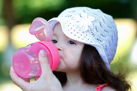 Adorable young children drinking water from a nursing bottle