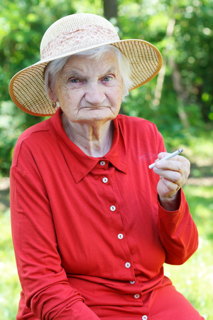 wrinkled: Elderly woman addicted to nicotine and smoking