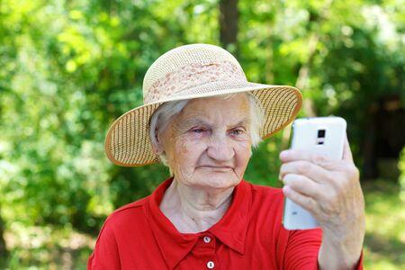 abuela: Hermosa mujer mayor mirando un tel�fono inteligente