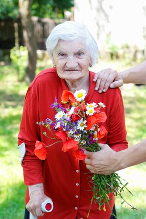 Caregiver giving a bouquet of flower to an elderly woman
