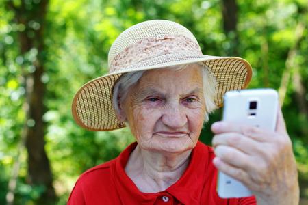 Mooie bejaarde vrouw kijken naar een smartphone Stockfoto