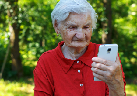 Beautiful elderly woman looking at a smartphone Banque d'images