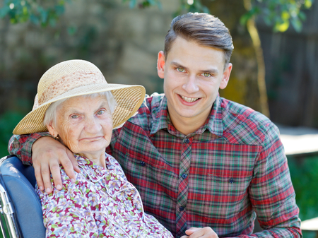 age care: Grandson hugging her beautiful senior wrinkled grandmother Stock Photo