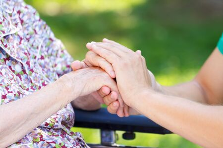 hand care: Young doctor hand holding an elderly womans hand Stock Photo