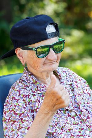 fashion trend: Senior woman wearing sunglasses and baseball cap