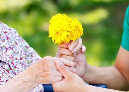 수석 여자에게 노란 꽃을주는 젊은이 스톡 콘텐츠