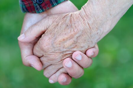 aiding: Young male hand holding an elderly womans hand