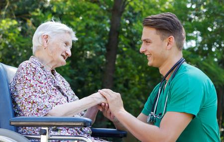 장애인 노인 여성을 돕는 젊은 의사 스톡 콘텐츠