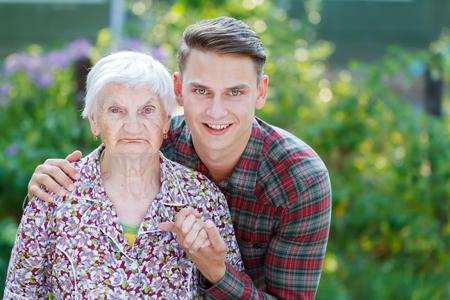 grandmother: Grandson hugging her beautiful  senior wrinkled grandmother