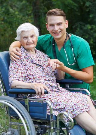 elderly patient: Young doctor helping a handicapped elderly woman Stock Photo