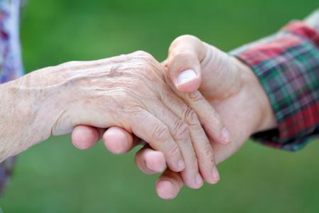 노인 여성의 손을 잡고 젊은 남성 손 스톡 콘텐츠