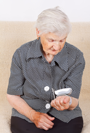 Elderly woman checking her own blood pressure Stock Photo