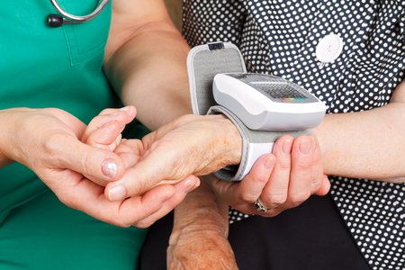 Female doctor checking senior woman blood pressure