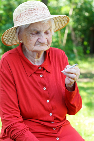 Elderly woman addicted to nicotine and smoking