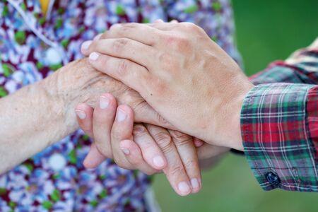 damas antiguas: Machos j�venes lado de la mano de una mujer mayor