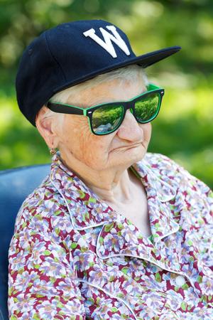 Senior woman wearing sunglasses and baseball cap