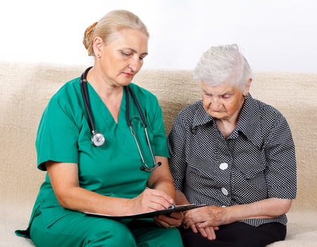 dementia: Picture of a senior woman talking with her caregiver