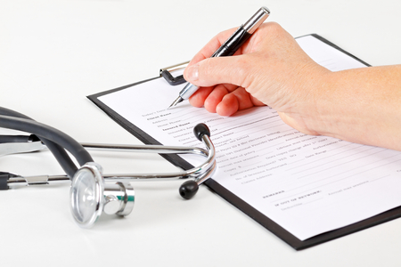medical record: Female doctors hand filling the medical record Stock Photo