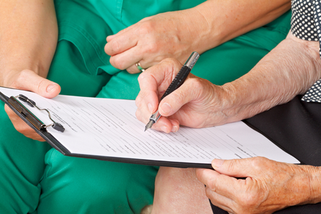 A senior womans hand signing a document Stock Photo