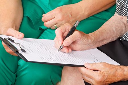 enfermera con paciente: La mano de una mujer mayor firma de un documento