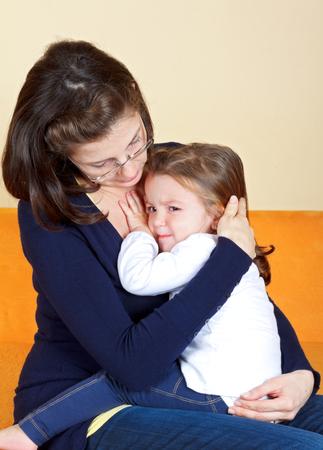 maltrato infantil: Ni�a asustada que abraza a su madre Foto de archivo