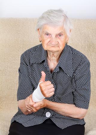 bandaged: A senior lady holding her bandaged wrist