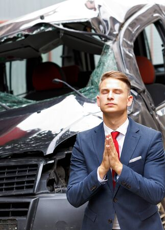 broken contract: Businessman praying in front of his damaged vehicle