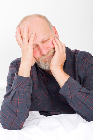 unbearable: Picture of a senior man having an unbearable headache Stock Photo