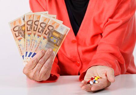 paying money: Senior woman paying money for medication
