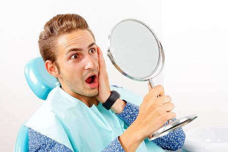 mirror: Surprised patient looking in the mirror after dental treatment Stock Photo