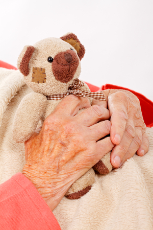 teddy bear love: Senior woman hand holding a brown teddy bear Stock Photo