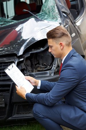 broken contract: Well dressed insurance assessor inspecting damaged vehicle