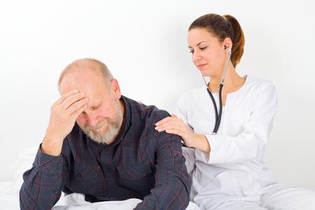 Nurse checking senior patient with stethoscope