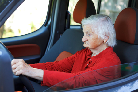 car on the road: Picture of a confident senior woman driving a car