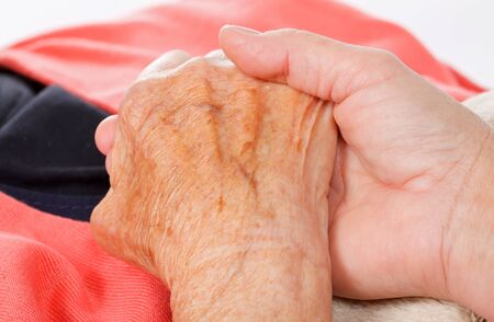 old hand: Caregiver holding elderly patients hand at home Stock Photo