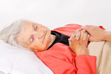 elderly: Caregiver holding elderly patients hand at home Stock Photo