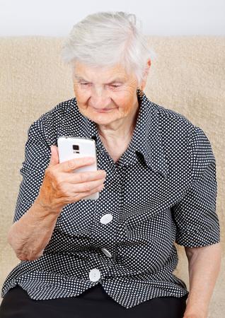 media gadget: Beautiful smiling senior woman looking at her smartphone Stock Photo
