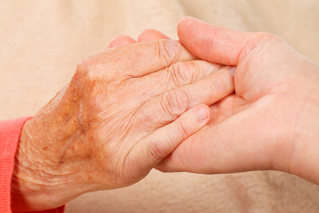 Caregiver holding elderly patients hand at home Stock Photo