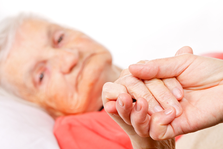 people with disabilities: Caregiver holding elderly patients hand at home Stock Photo