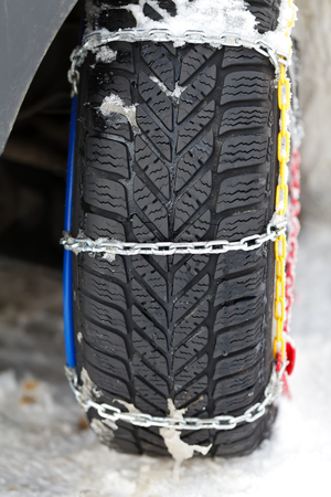 icy conditions: Photo of a vehicle tyre with snow chains on a frozen road