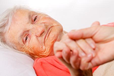 집에서 노인 환자 손을 잡고 간병인