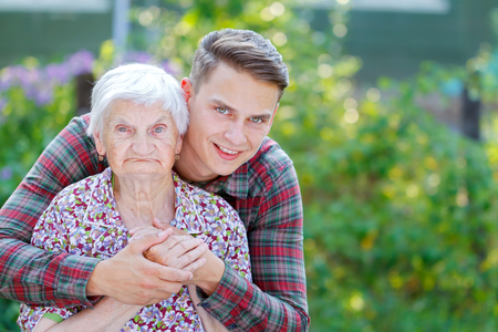 Grandson hugging her beautiful  senior wrinkled grandmother
