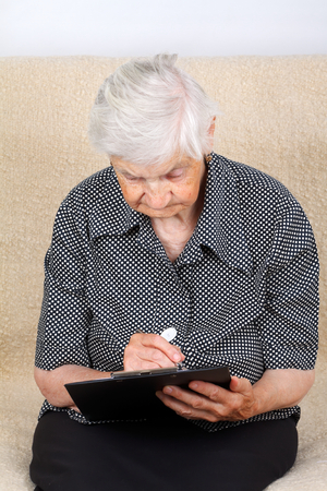 medical record: Elderly woman analysing her medical record Stock Photo